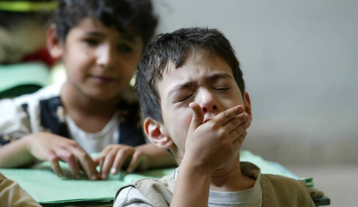 A blind Iraqi boy yawns as his classmate